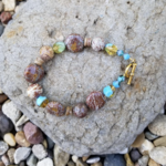 Beaded blue and brown bracelet with gold toned toggle closure. is being swapped online for free